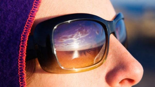 Девушка в темных очках смотрит на закат.